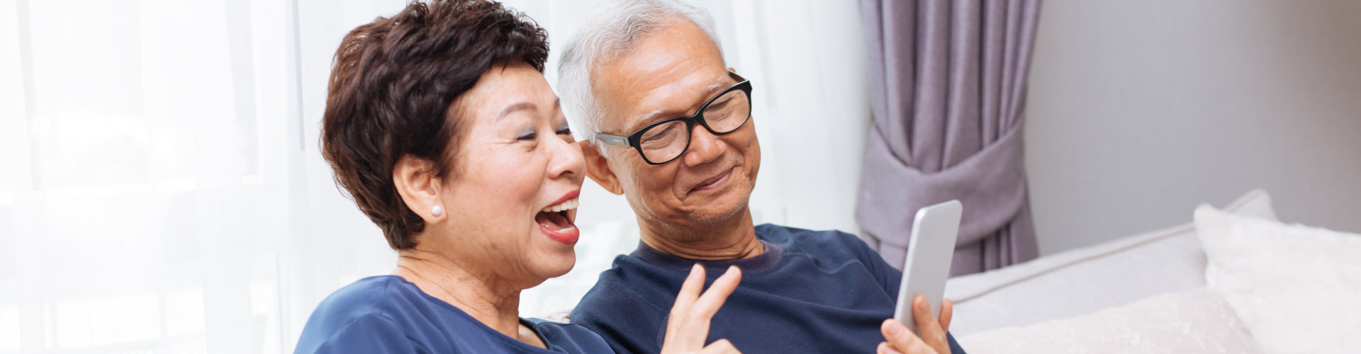 senior man and woman looking at the phone